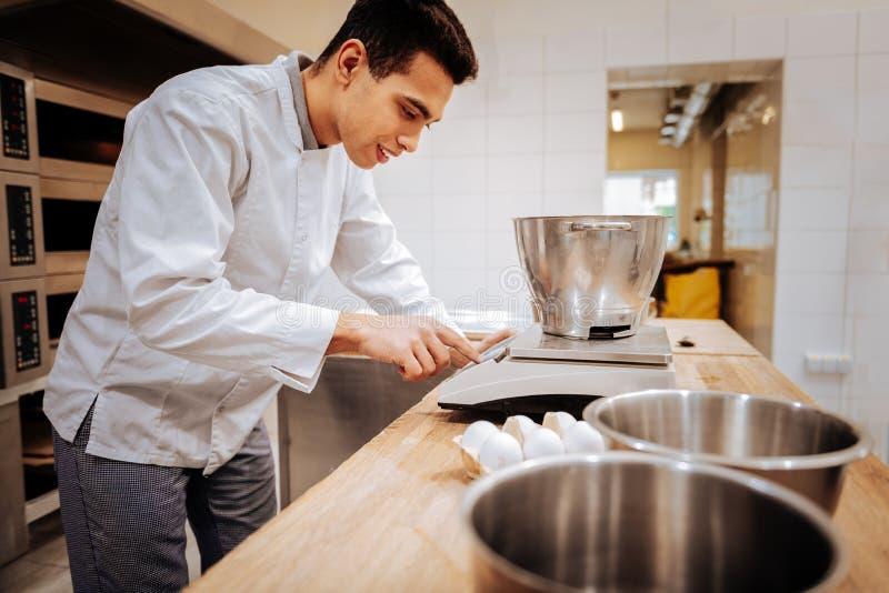 Bärande vitt omslag för bagare genom att använda modern kökvåg royaltyfri fotografi