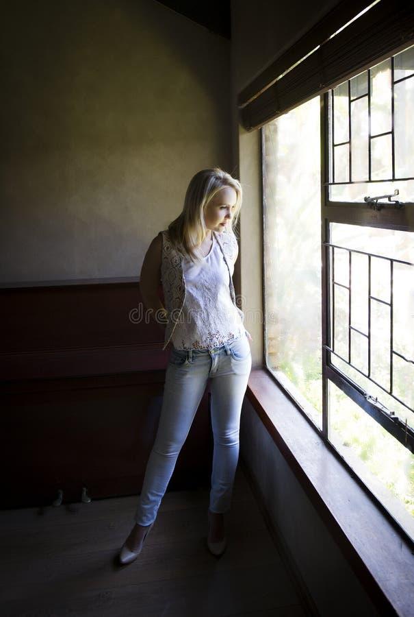 Bärande waistcoat för sexig blond kvinna som poserar bredvid fönster med hennes händer i hennes fack royaltyfri foto