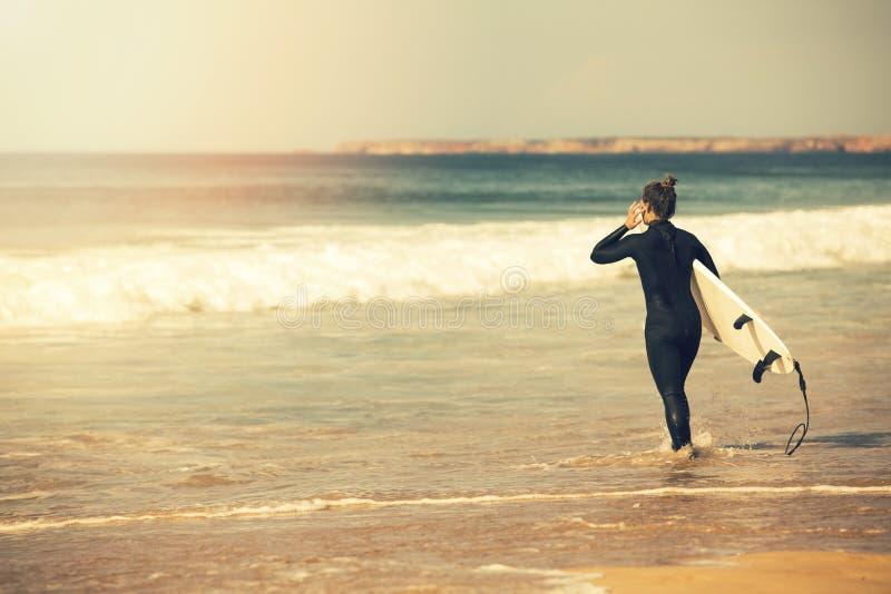 bärande wetsuit för ung surfareflicka som går in i havet royaltyfri foto