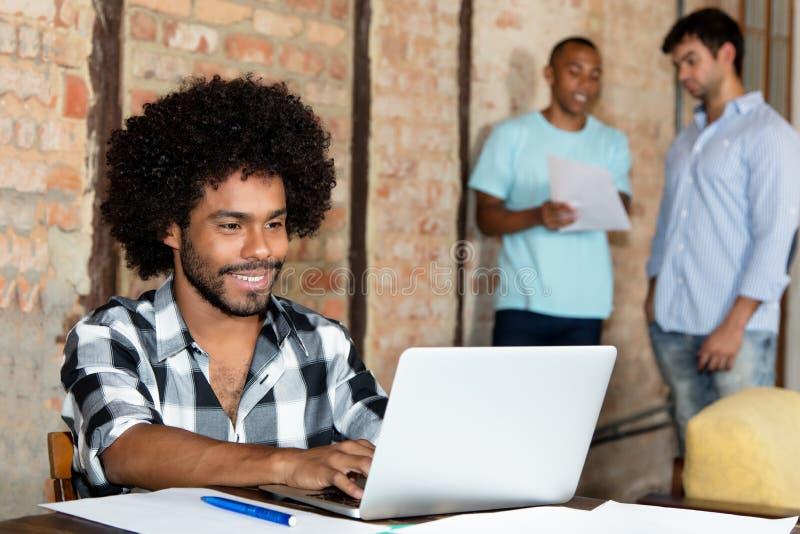 Bärare för afrikansk amerikanhipsterprogramvara med bärbara datorn på arbete arkivbilder