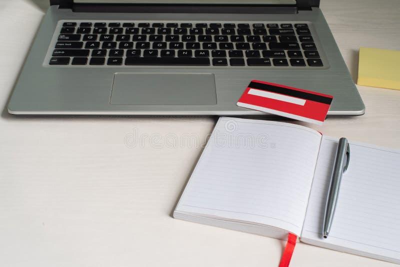 Bärbar dator öppen anteckningsbok, penna, kreditkort, pappersanmärkning arkivfoton