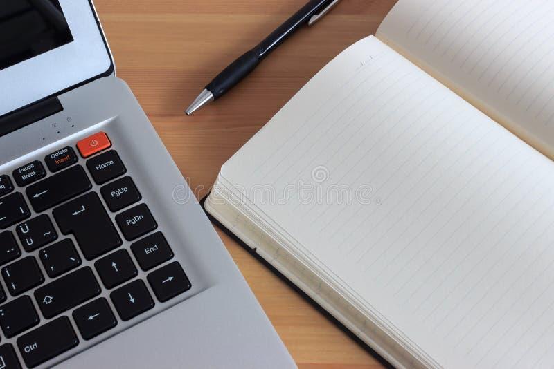 Bärbar dator, anteckningsbok och penna på trätabellen royaltyfria bilder
