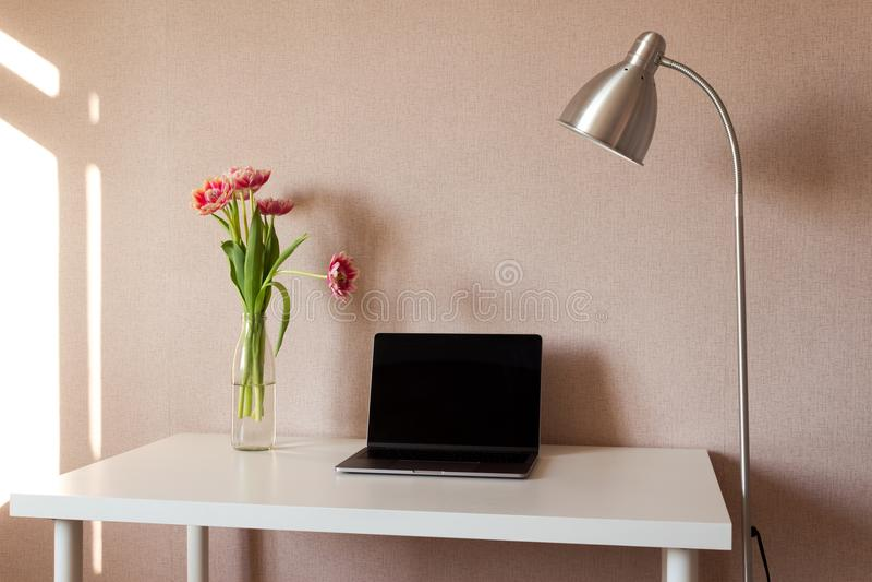 Bärbar dator, bukett av tulpan och metallisk lampa på den vita tabellen royaltyfria bilder