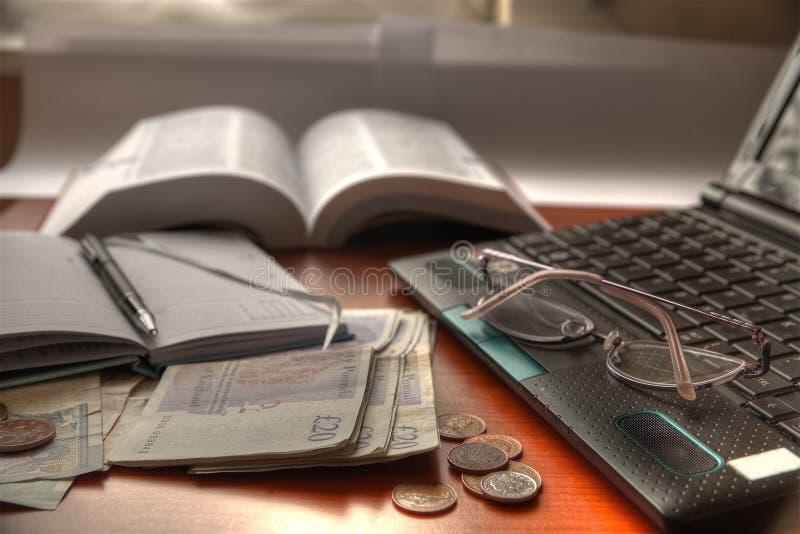 Bärbar dator, exponeringsglas, anteckningsbok och pengar. royaltyfri fotografi