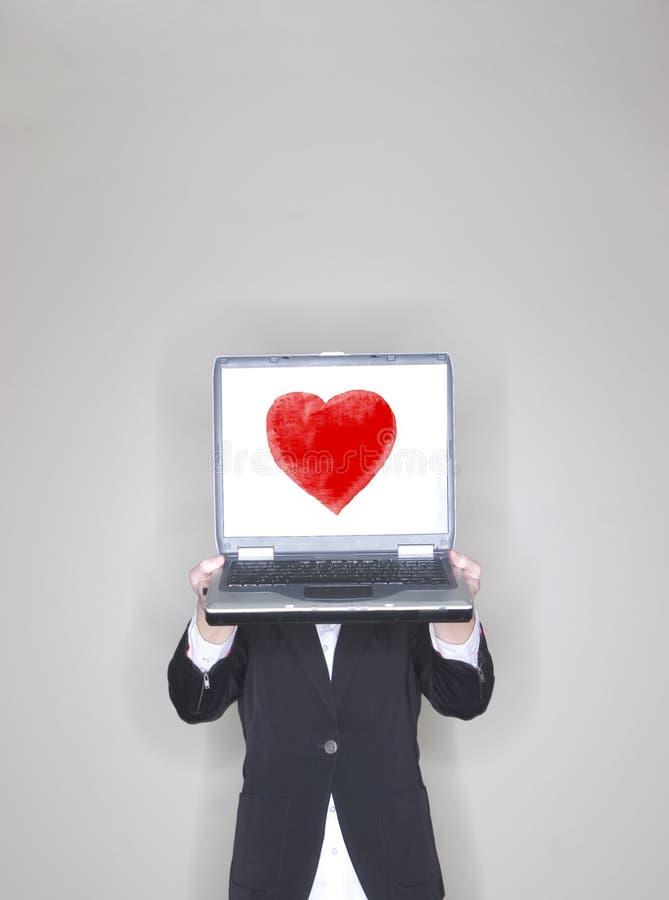 bärbar dator för affärskvinnahjärtaholding arkivfoto