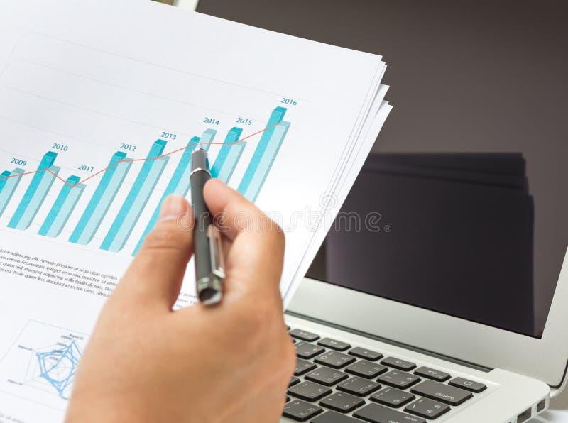 Bärbar dator för affärspersonbruk med det finansiella diagrammet arkivbilder