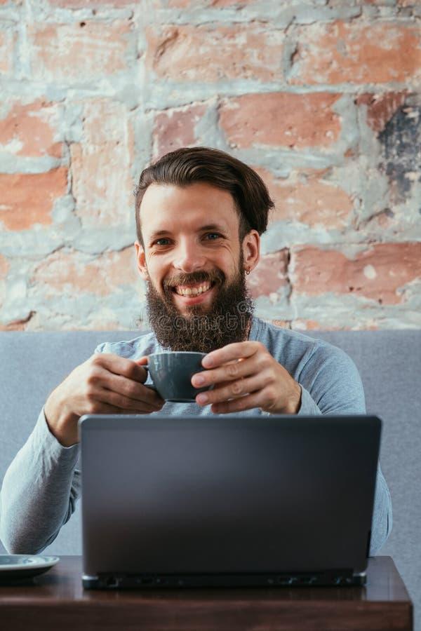 Bärbar dator för drink för kopp för håll för man för arbete för kaffeavbrott varm arkivfoton