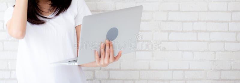 Bärbar dator för innehav för anseende för kvinna för banerwebsite asiatisk på tegelstenceme royaltyfri foto