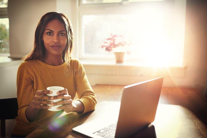 Bärbar dator för kaffe för allvarlig kvinna hållande öppen nära arkivbild