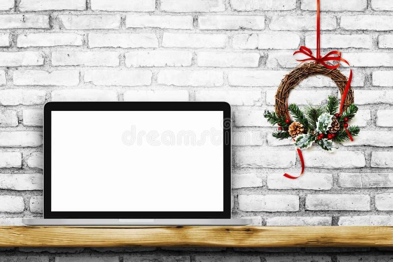 Bärbar dator för tom skärm på den vita tegelstenväggen med julkransen arkivfoto