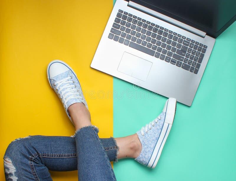 Bärbar dator, kvinnliga ben i jeans och gymnastikskor på en kulör pastellfärgad bakgrund, minimalism, plan lekmanna- stil royaltyfri bild