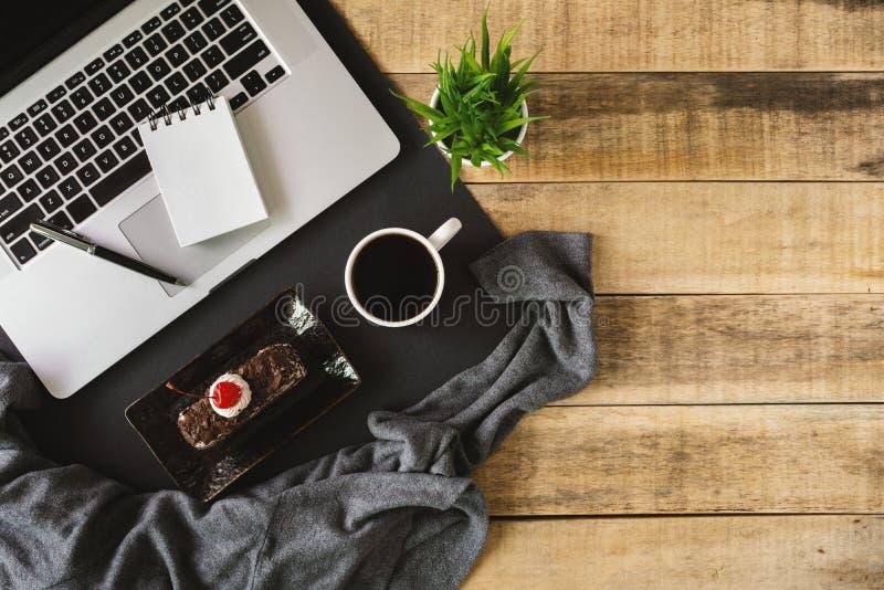 Bärbar dator, liten anteckningsbok och frukost på wood bakgrund arkivfoto