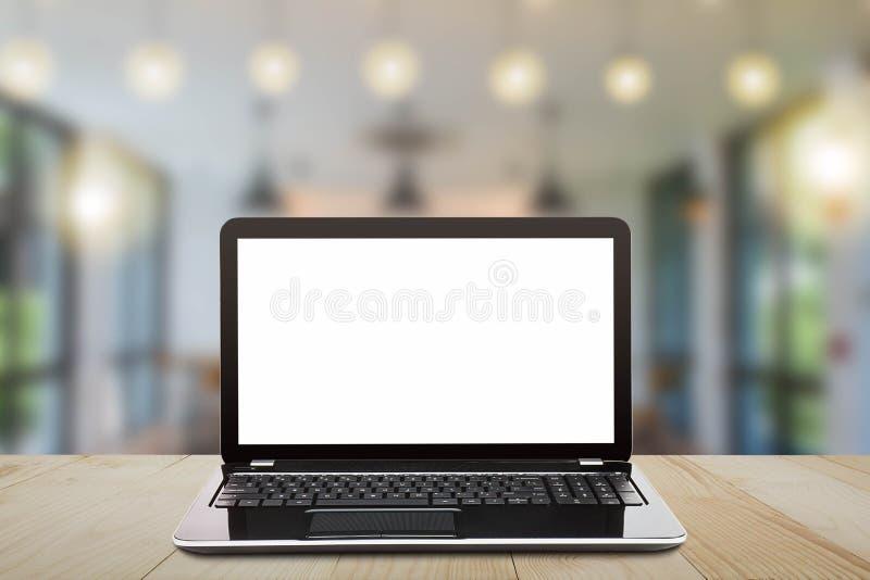 Bärbar dator med den tomma vita skärmen på tappningträtabellen på suddig coffee shopbakgrund arkivfoto