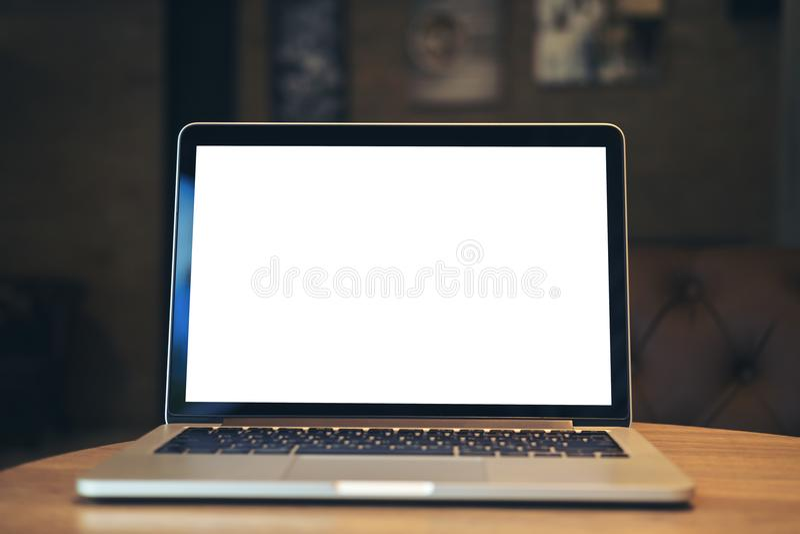 Bärbar dator med den tomma vita skärmen på trätabellen i mörkt modernt kafé arkivfoto