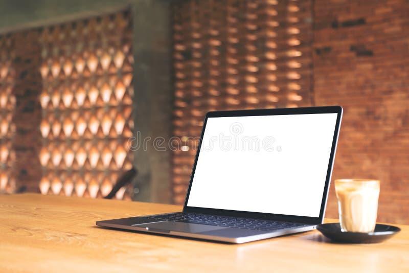 Bärbar dator med den tomma vita skrivbords- skärm- och kaffekoppen på trätabellen med bakgrund för tegelstenvägg arkivbild