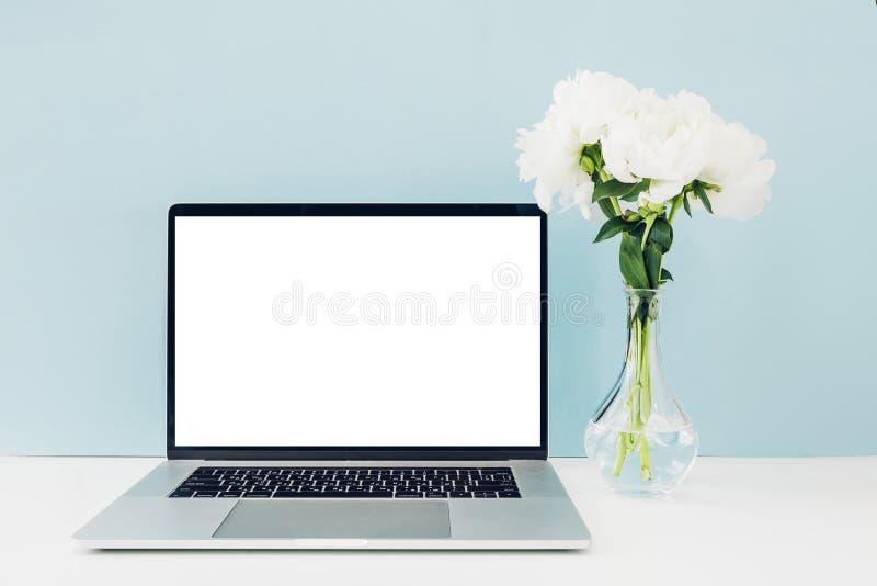 Bärbar dator med den vita tomma skärmen och blommor i vas på tabellen på blå bakgrund Åtlöje upp arkivfoto