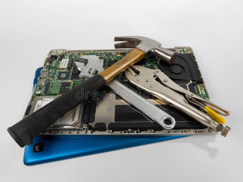 Bärbar dator med hammaren, skruvnycklar och låsaplattång arkivbild