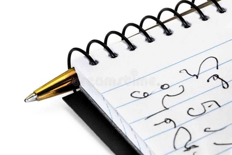 Bärbar dator med Shorthand och penna över vitt royaltyfria bilder