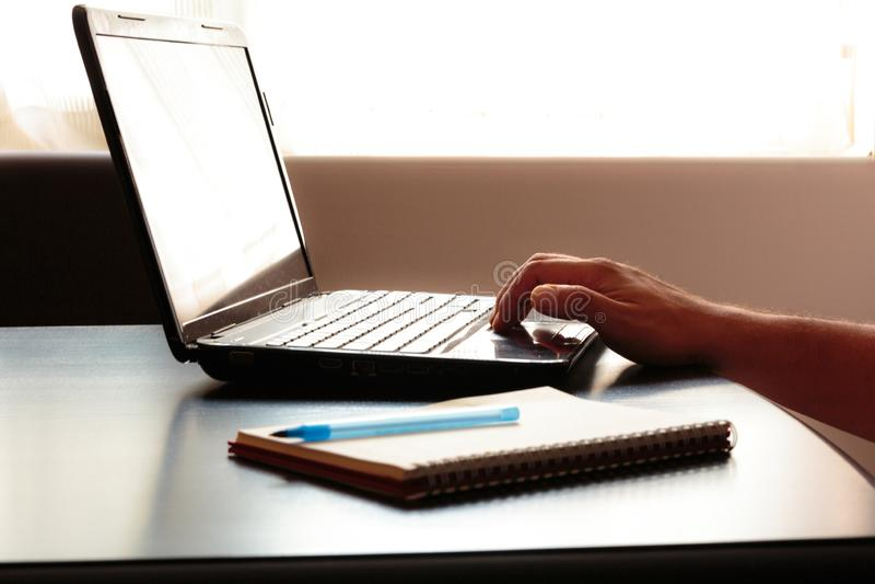 Bärbar dator och anteckningsbok med pennan på ett skrivbord arkivbilder