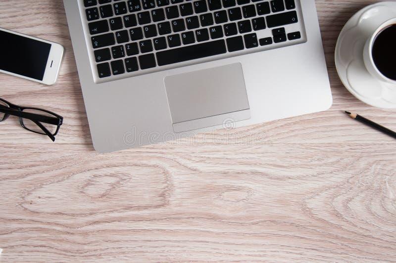 Bärbar dator- och kaffekopp på den wood tabellen royaltyfria foton