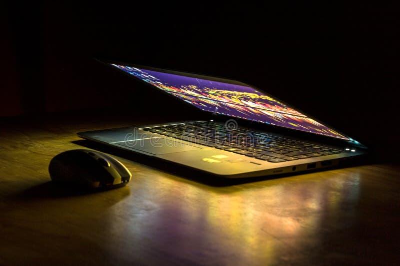 Bärbar dator och mus i mörkret arkivfoton