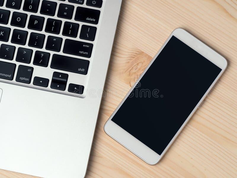 Bärbar dator och smartphone på trätabellen arkivfoton