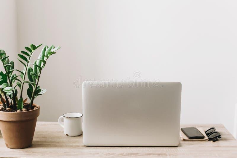 Bärbar dator på träskrivbordet med telefonen, anteckningsboken, kaffekoppen och pl arkivbilder