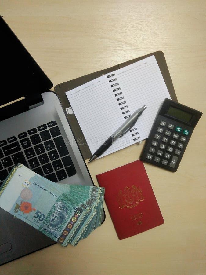 Bärbar dator pengar, pass, penna, räknemaskin, skrivbord, anteckningsbok med tomma sidor royaltyfri bild