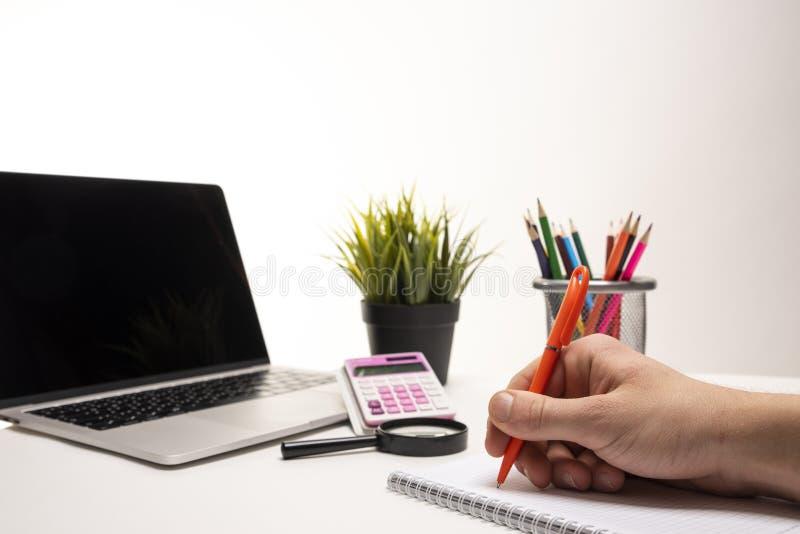 Bärbar dator, räknemaskin, förstoringsapparat, organisatör, färgpennor, grön växt, notepad och en hand som rymmer en penna, medan arkivbild