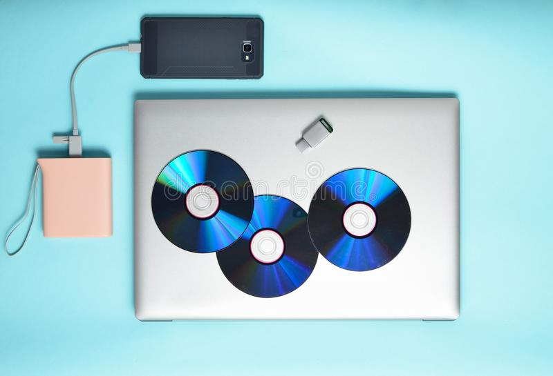 Bärbar dator smartphone, maktbank, CD drev, USB exponeringsdrev på en blå bakgrund Modernt och omodernt digitalt massmedia och gr royaltyfri bild