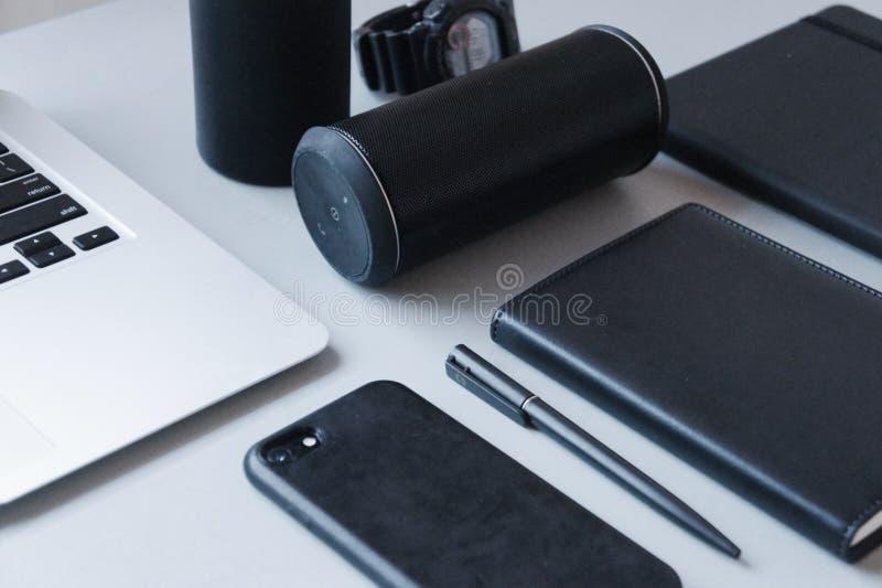 Bärbar dator, svart telefon, svart anteckningsbok och svart penna med den svarta högtalaren på den vita tabellen, närbild, kontor royaltyfria bilder