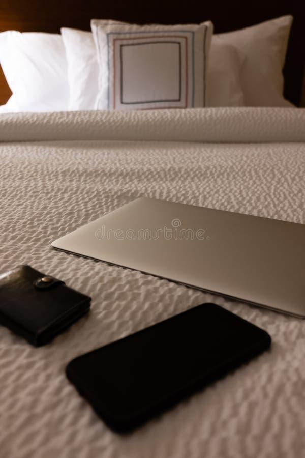 Bärbar dator, telefon och plånbok på hotellsäng royaltyfri bild