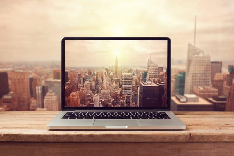 Bärbar datordator över New York City horisont Retro filtereffekt arkivbilder