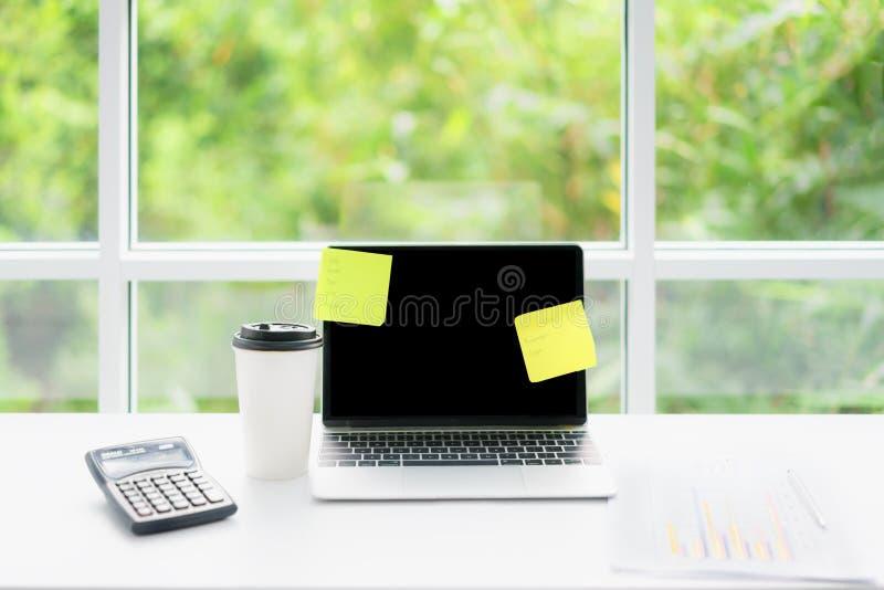 Bärbar datordator för tom skärm och kaffekopp på tabellen på kaffekafét med naturen i bakgrund Teknologi, affär och modernt arkivfoton