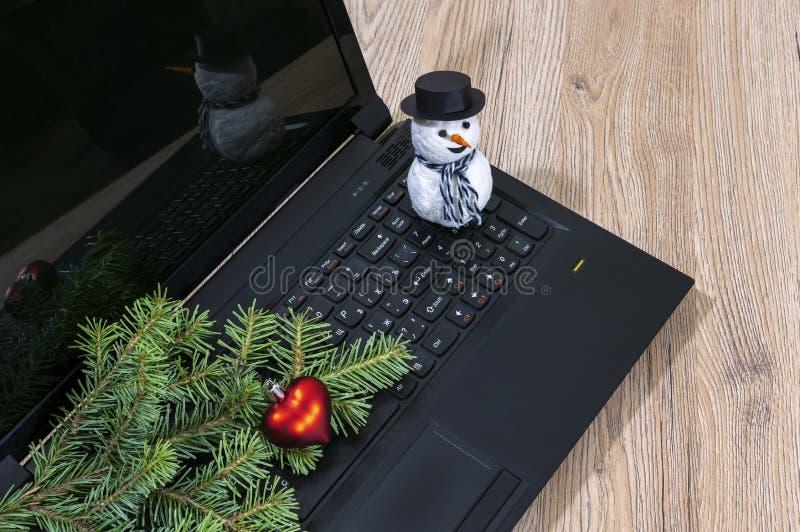 Bärbar datordator, julgranfilial och en snögubbe på ett trä royaltyfri foto