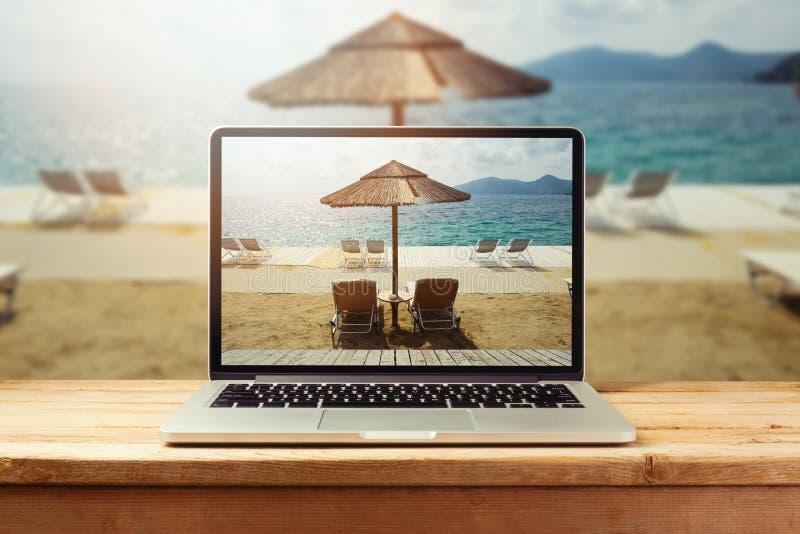 Bärbar datordator med solig strandbild på trätabellen Foto för sommarsemester royaltyfri fotografi