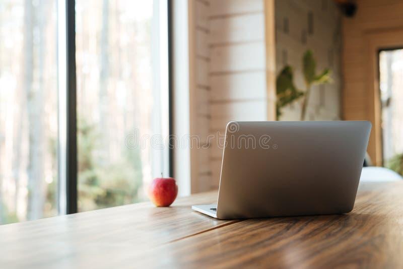 Bärbar datordator på tabellen inomhus nära äpplet och fönster arkivbilder