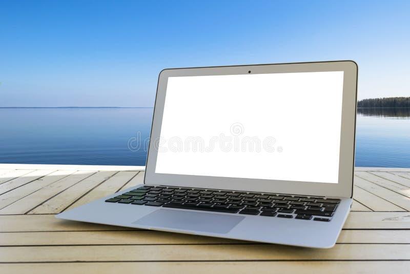 Bärbar datordator på trätabellen Bästa havsikt tropisk bakgrundsö Öppna tomt tomt utrymme för bärbar datordatoren Bekläda beskåda royaltyfria foton