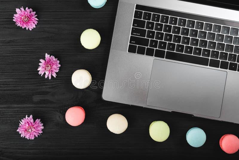 Bärbar datordator, rosa färgblommor och macarons på ett träskrivbord, kopieringsutrymme för bästa sikt arkivfoto