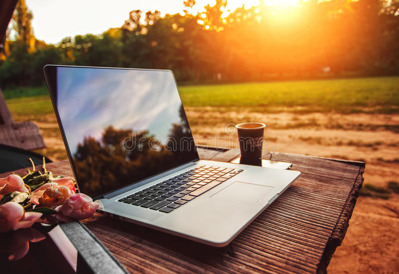 Bärbar datordatoren på den grova trätabellen med kaffekoppen och bukett av pioner blommar i utomhus- parkerar arkivfoto