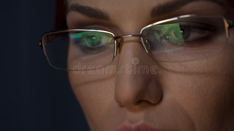 Bärbar datorskärm reflekterad i exponeringsglas, kvinnligt arbete på datoren, koncentration royaltyfri fotografi