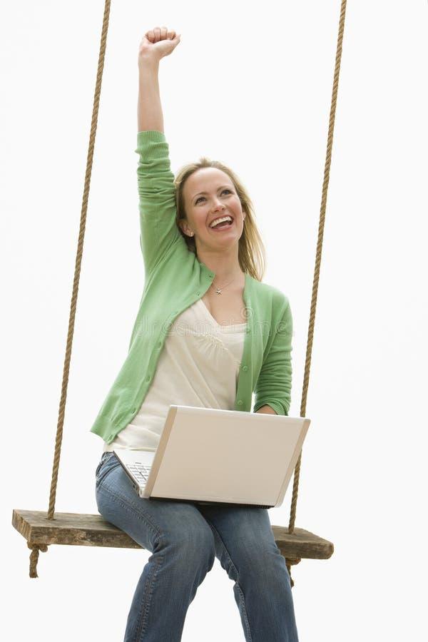 bärbar datorswing genom att använda kvinnan royaltyfri foto