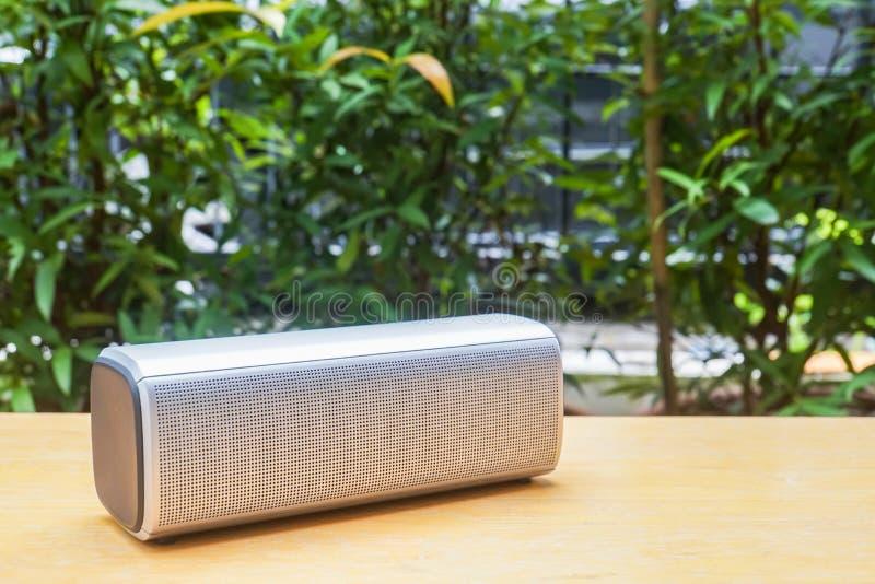 Bärbar högtalare för trådlös bluetooth på trätabellen i hemträdgård royaltyfri foto