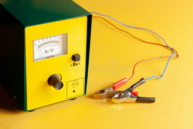 Bärbar recharger för bilbatteri Nära övre uppladdare med röda och svarta gem Gul bakgrund uppladdning urladda utrustning arkivbild