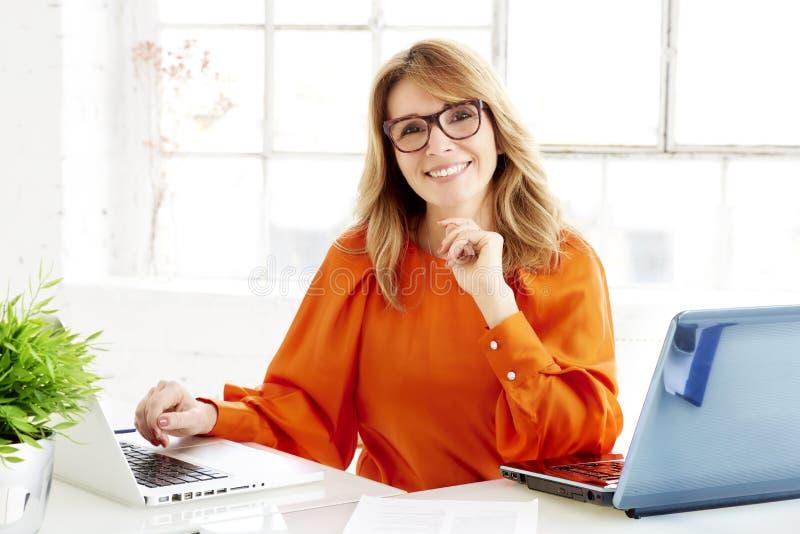 Bärbara datorer för affärskvinna för investeringrådgivare arbetande i kontoret, medan se kameran och att le royaltyfri foto