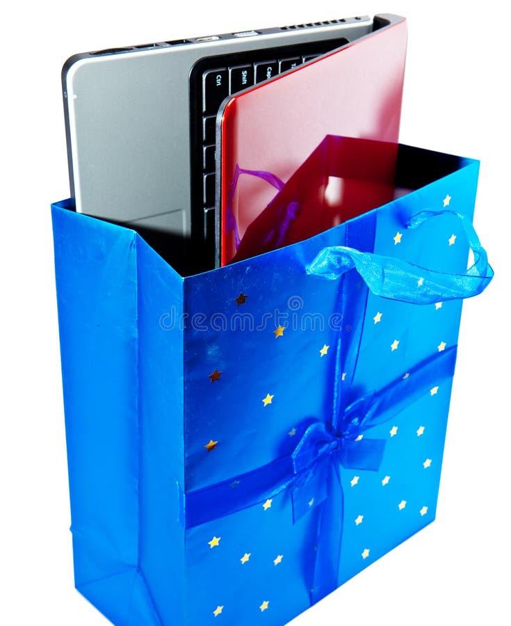 Bärbara datorn i en gåvapacke. Slut upp på en vit bakgrund arkivbild