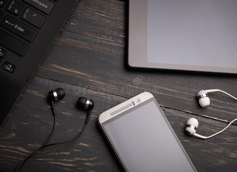 Bärbara datorn ilar telefonen, minnestavlaPC och hörlurar med mikrofon royaltyfria bilder