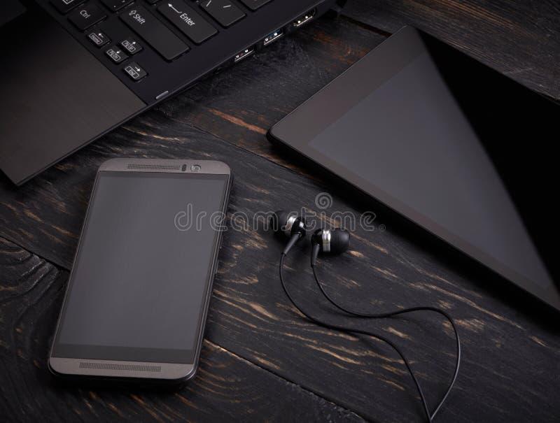 Bärbara datorn ilar telefonen, minnestavlaPC och hörlurar med mikrofon royaltyfri bild