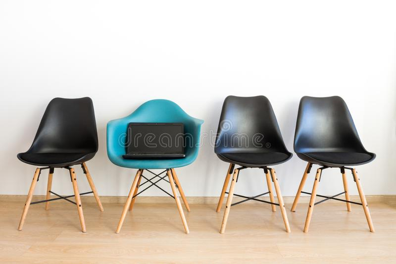 Bärbara datorn på en stol Blå stol bland svart på en vit bakgrund arkivbilder