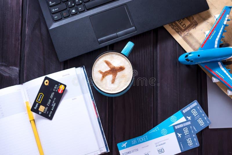 Bärbara datorn plana biljetter, kaffe, kreditkort ligger på tabellen arkivfoto